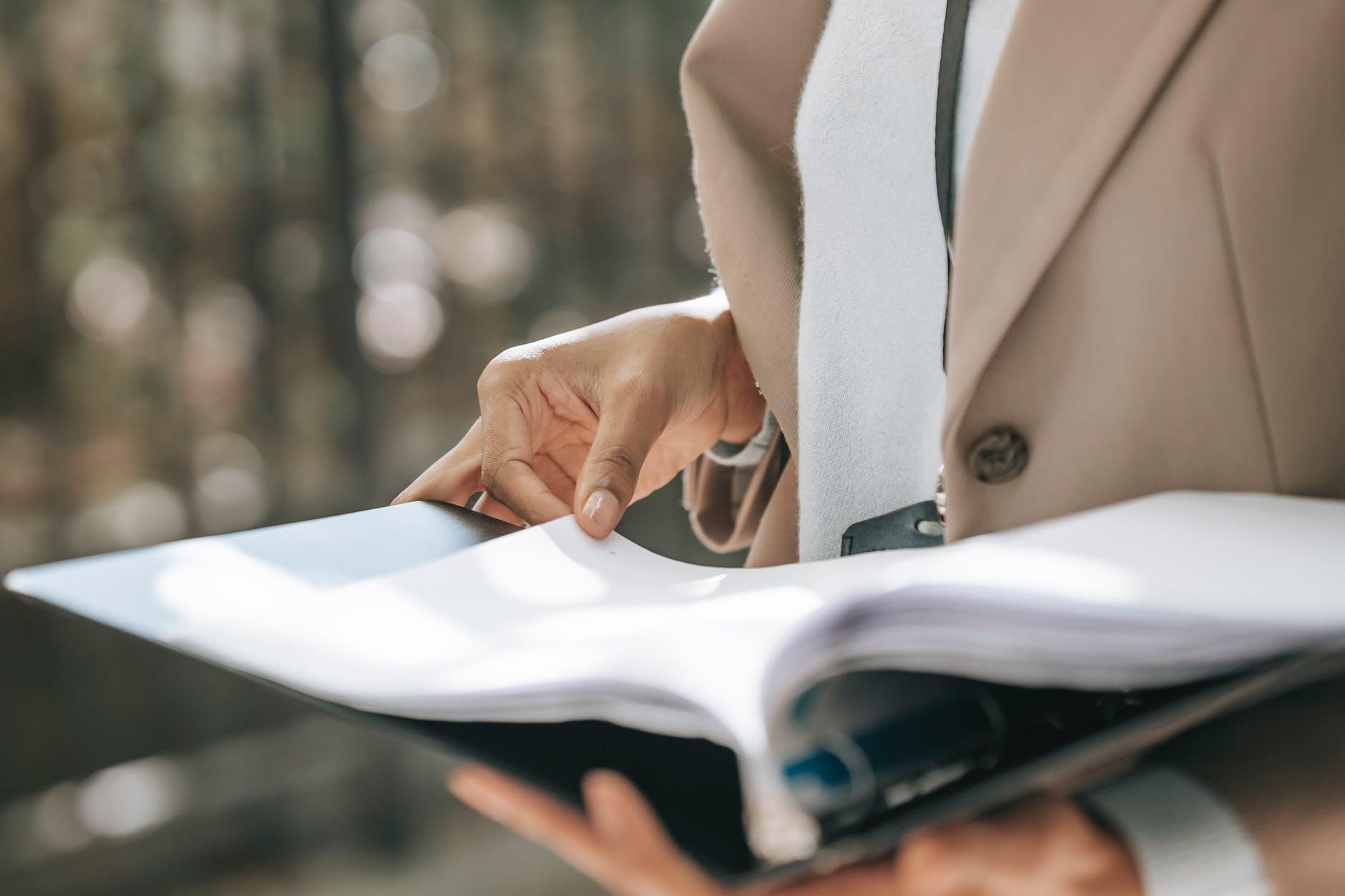 crop businesswoman looking through documents